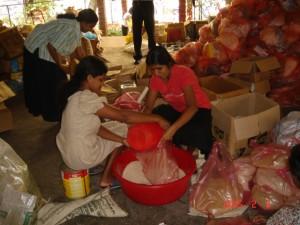 各村々に送るために小麦粉やお米を分類するボランティアの人々